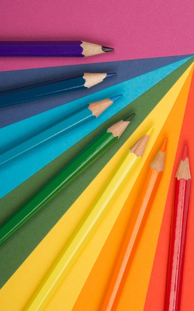 differently: rainbow background of differently colored papers and pencils