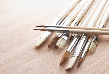 Paint brushes on wooden background, brushes on wooden table   photo