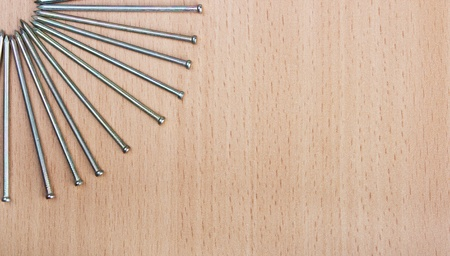 Nails on wooden background, close up photo