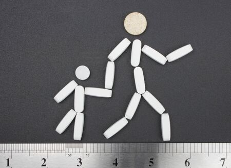 tablet-man and child, symbol for drugs and medicine, walking on the ruler  photo