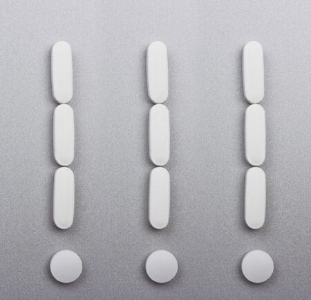 White pills laid out in the form of exclamation marks on gray background  photo