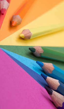 rainbow background of differently colored papers and pencils