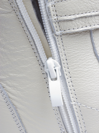 Abstract white leather background with seams and zip, closeup photo