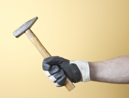 The hand in  worker glove holding the hammer  photo