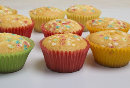 freshly baked sweet muffins in colorful papers on the table  photo