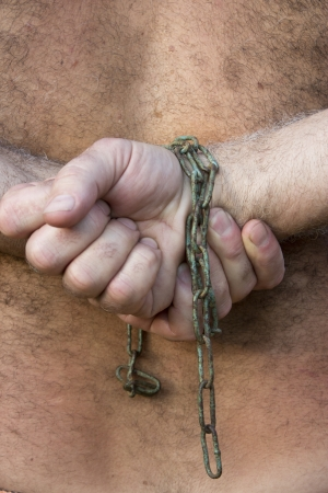 mans hands tied with chains on the back photo