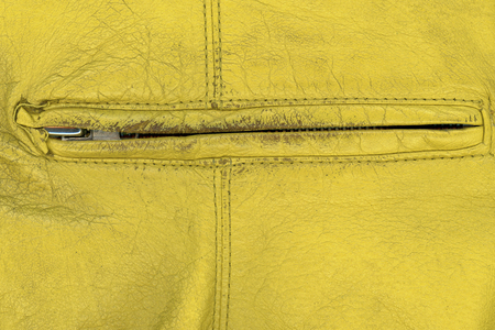 Extreme close up shot of yellow old hand bag zipper photo