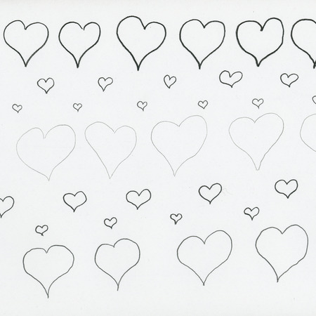 hearts drawn in pencile on white textured paper backgrownd
