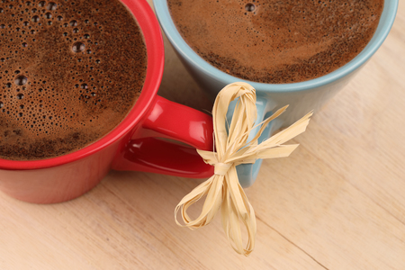 two colorful caps of coffee connected together with ribbon made of natural straw Stock Photo