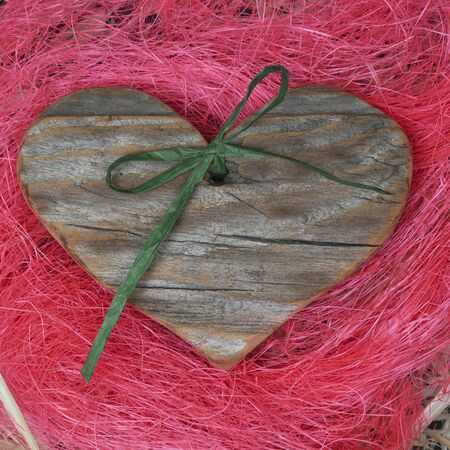Wooden heart on pink straw background, decorated Stock Photo