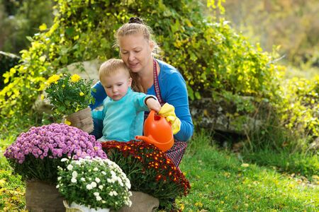 Young woman with a child are planting flowers in the garden photo