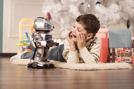 robot toy: Boy with Christmas gifts under the tree
