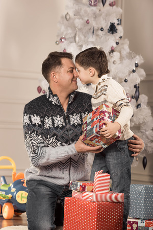 man giving his son a Christmas gift under the tree photo