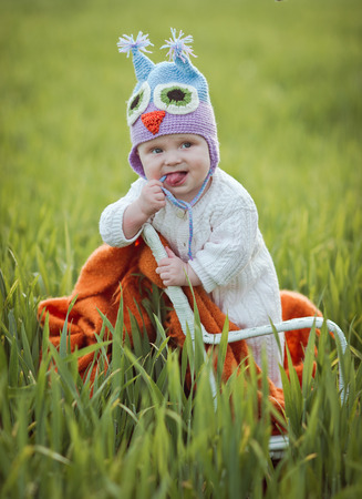 boy on a chair in a field. boy in a knitted hat. photo