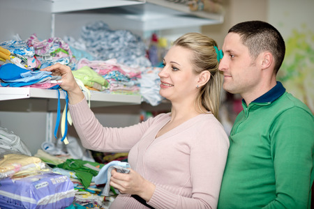 impregnated: Pregnant woman buying baby clothes in supermarket .  Young pregnant woman choosing newborn clothes Stock Photo
