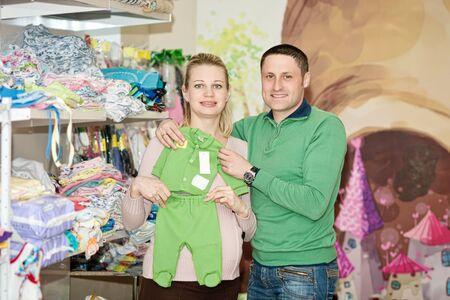 impregnated: Donna incinta acquisto di vestiti per bambini in un supermercato. Giovane donna incinta che sceglie i vestiti appena nati