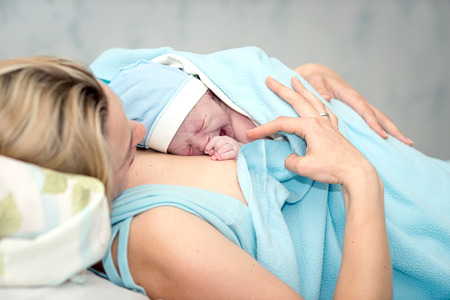 nacimiento bebe: Mujer hermosa joven con un beb� reci�n nacido despu�s del nacimiento Foto de archivo