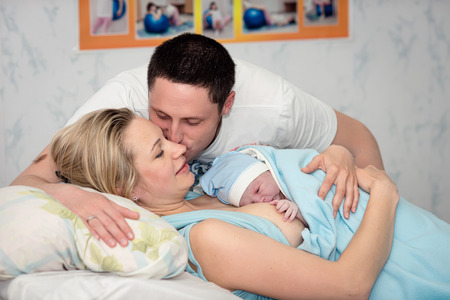 Young beautiful woman with a newborn baby after birth Standard-Bild