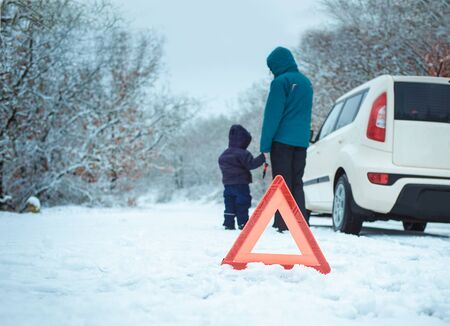 woman with a child on the winter road. emergency sign Standard-Bild
