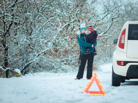 emergency sign: woman with a child on the winter road. emergency sign Stock Photo