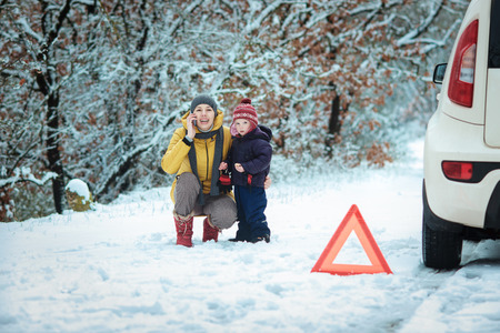 woman with a child on the winter road. emergency sign Reklamní fotografie