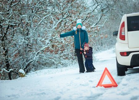 woman with a child on the winter road. emergency sign photo