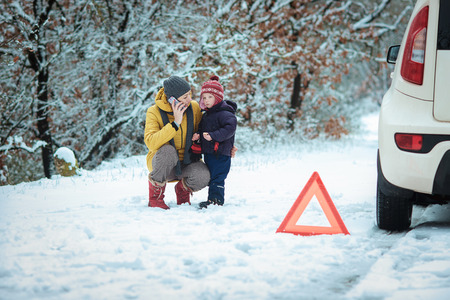 woman with a child on the winter road. emergency sign Reklamní fotografie - 36813296