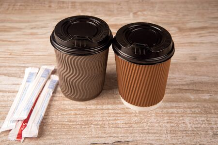 to go cup: coffee in a paper cup. sugar paper sticks