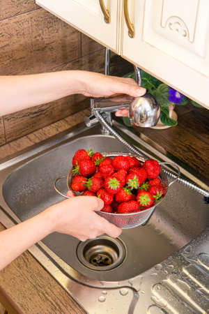 Strawberry girl washes in the sink