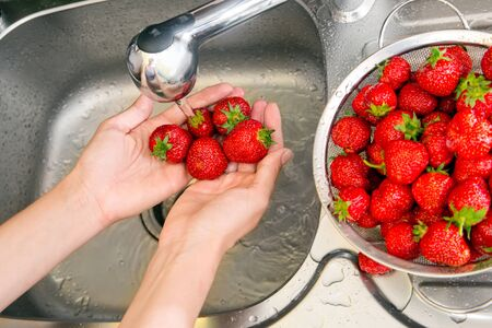 Strawberry girl washes in the sink photo