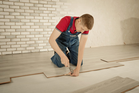 Installation laminate. focus on the hand. Man puts laminate Standard-Bild