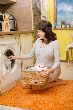 tricot: Happy pregnant woman washes baby clothes.