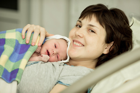 happy woman after the birth of a newborn baby on a functional bed
