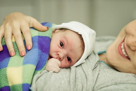 recien nacido: mujer feliz despu�s del nacimiento de un beb� reci�n nacido en una cama funcional