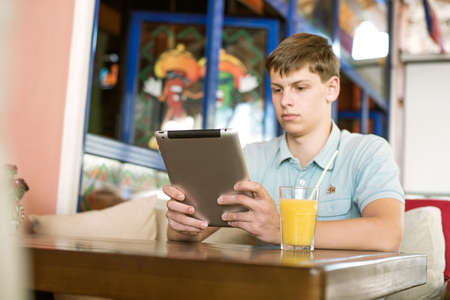 Handsome young man with laptop in a cafe photo