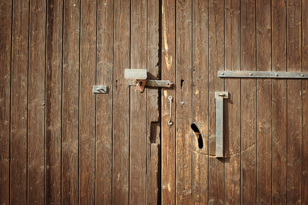 old wooden door with a metal lock. Background texture photo