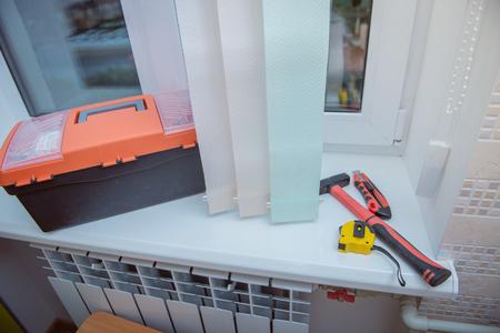 男は窓のブラインド、垂直ブラインドをインストールします。 写真素材