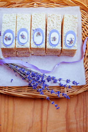 Slices of cake and bouquet of lavender on a wooden table