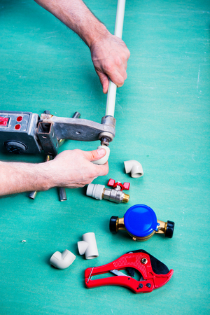 Soldering iron for polypropylene plumbing pipes. The hands of the plumber are holding the pipeline parts. closeup