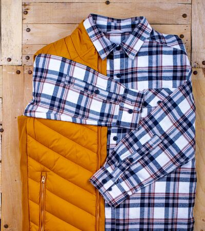 Winter mens clothes and accessories on a wooden background.  warm winter jacket and mens shirt Reklamní fotografie