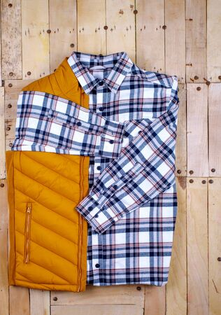 Winter men's clothes and accessories on a wooden background. 