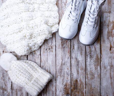 ropa de invierno blanca para mujer sobre fondo de madera Foto de archivo