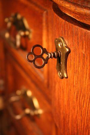 insure: antique brass key in chest, desk, dresser Stock Photo