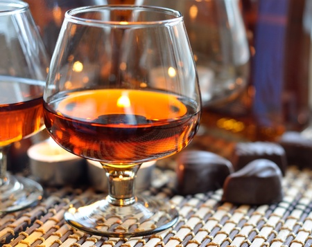 a glass of brandy, sweet and a candle photo