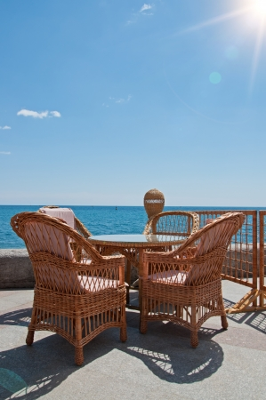 Table and rattan chair by the sea. Yalta, Cremea Stock Photo - 9805525