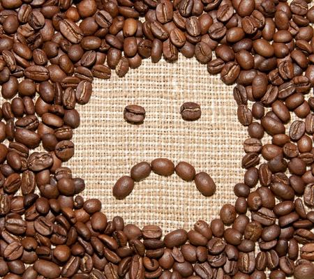 lamentable: coffee beans sad smile on burlap background Stock Photo