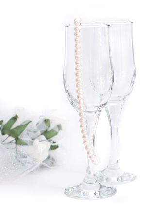 Empty glasses, pearls and a bouquet of flowers on a white background Stock fotó