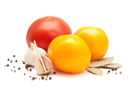 Three tomatoes - one red and two yellow, garlic, bay leaf, coriander, pepper, isolated on a white background photo