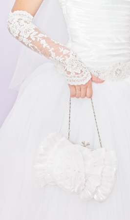 Young bride holding a small white handbag  photo