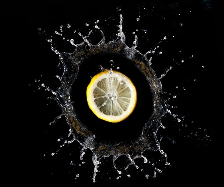 Lemon falling into water on black background photo